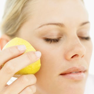 Close-up of a woman rubbing half a lemon to her cheek